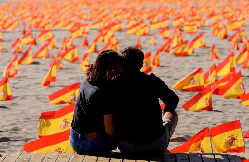 西班牙新冠肺炎確診破百萬例,圖為一對情侶坐在數千西班牙國旗旁,相互親吻。(Getty Images)