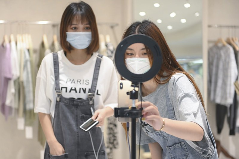 廣州服裝批發市場內,主播正在店內直播。(中新社)