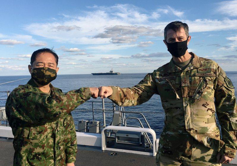 駐日美軍指揮官施奈德(右)26日在加賀號上,與日本統合幕僚長山崎幸二(左)碰拳致意,遠方是雷根號航空母艦。(路透)
