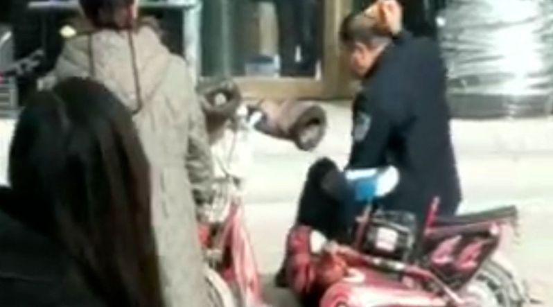 山西朔州一男子當街將妻子按在地上用石頭猛砸,女子掙扎反抗但無法掙脫。此舉引來不少路人圍觀,但無人上前勸阻。(視頻截圖)