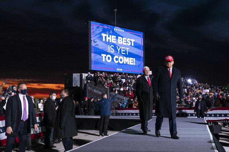 拼連任的川普總統在投票前夕連趕六場催票造勢活動,在晚上與副總統潘斯首次合體,在關鍵州密西根州Traverse市同台競選,向支持者揮手。(美聯社)