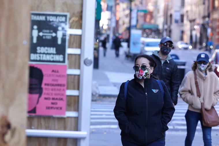 圖為紐約市民眾戴著口罩、保持社交距離。路透