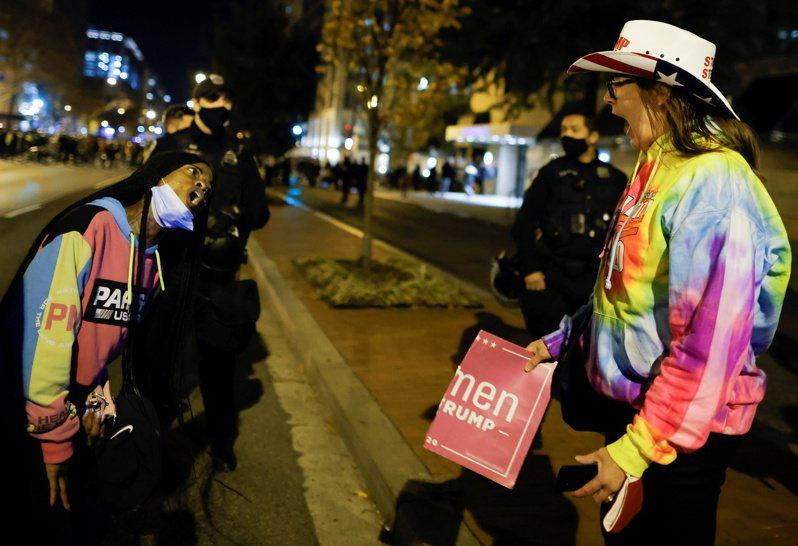 挺川普大遊行14日結束後,支持者(右)被反川者(左)包圍,在華府街頭相互爭罵大選輸贏。警方加強戒備。(路透)