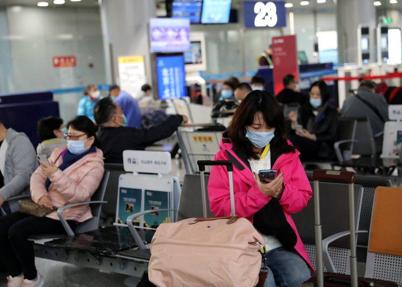 多達60%的美國民眾認為,中國應在全球負起新冠疫情的賠償責任;圖為在北京首都國際機場,戴口罩的旅客在等待登機。(路透)