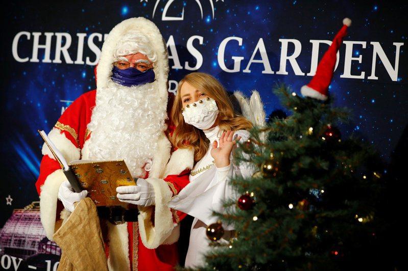 聖誕節與新年假期將至 ,憂心疫情大爆發的專家表示,必須記取感恩節教訓,重新修正公衛警告訊息傳遞方式。圖為聖誕老人和天使的扮演者也戴起口罩。路透