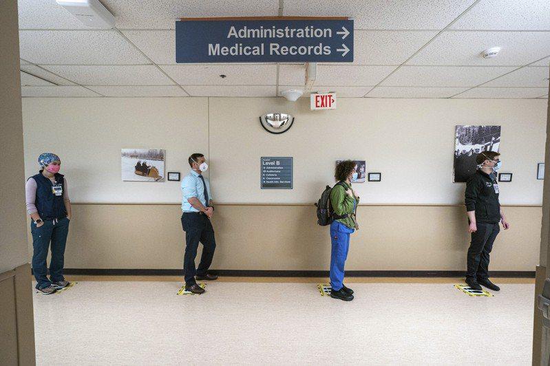 全美新冠肺炎確診數字續攀升,16日有11萬3069人染疫住院,連續十天創新高。圖為民眾16日在安格拉治的阿拉斯加醫療中心排隊接種疫苗。(美聯社)