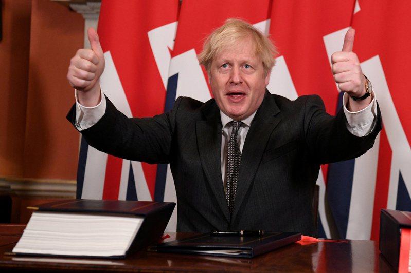 英國首相強生(見圖)2020年12月30日在倫敦首相府簽署英國與歐盟貿易協議後,豎起雙手大拇指。(路透)