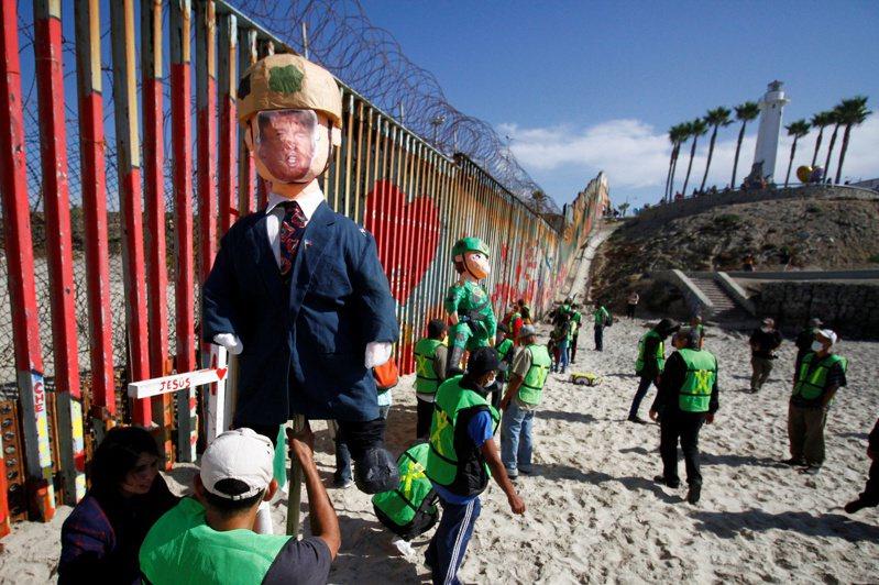 圖為墨西哥蒂華納的邊牆抗議者早前豎起川普和邊境人員造型的人偶。(路透)