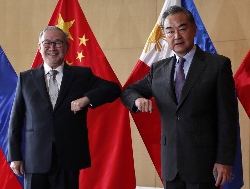 中國外交部長王毅(右)16日在馬尼拉與菲律賓外長陸辛(左)會面,承諾將捐贈50萬劑新冠疫苗給菲國。(中央社)