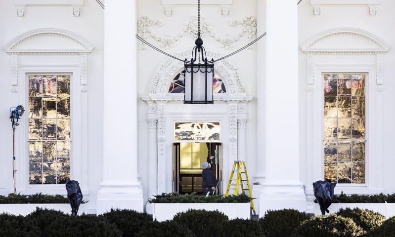 拜登已陸續將眾多行囊運進白宮,一名清潔人員正在清洗門廊。(歐新社)