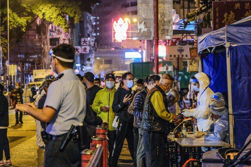 24日傍晚6時起,九龍佐敦受限制區域有限度解封。圖為檢測獲陰性結果的市民陸續離開該區域。(中通社)