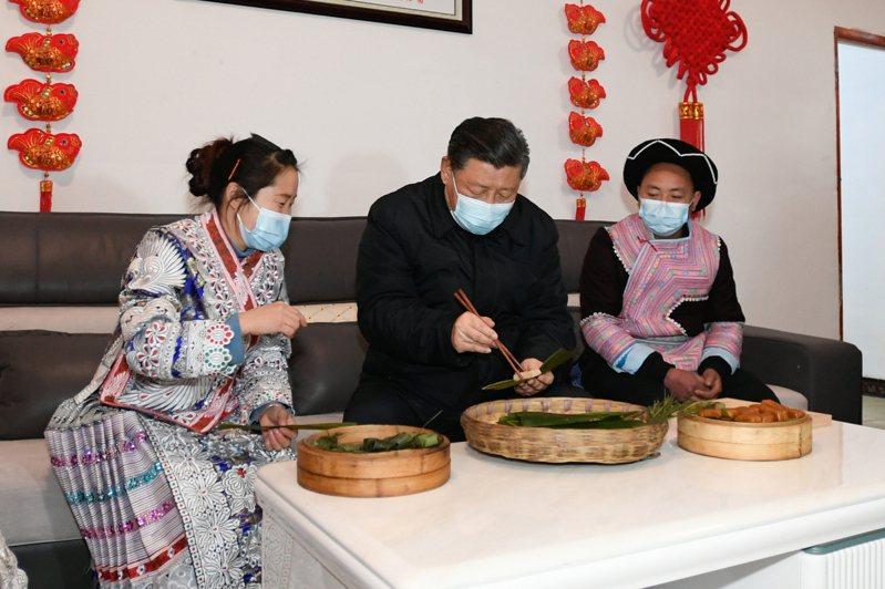 習近平在苗族村民趙玉學家,與一家人在客廳邊聊家常邊製作當地傳統節日食品黃粑。(新華社)