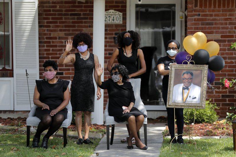 全美因新冠病毒病歿人數22日達到50萬人的里程碑。去年4月疫情正熾,在紐奧良的哈蒙家人在家人向開車經過悼念的親友揮手致謝。哈蒙因為新冠去世。(美聯社)
