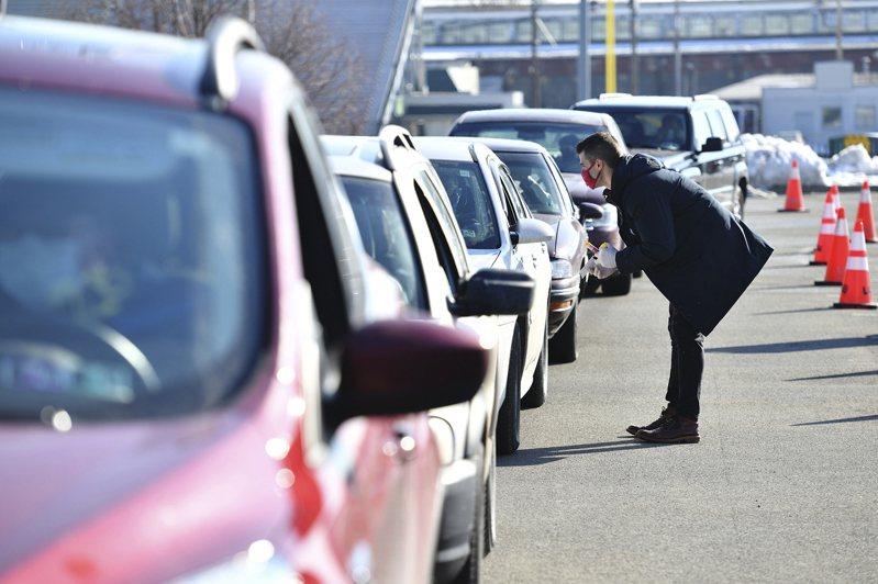 全美檢測人數陡降,令人擔心會增加民眾感染風險。圖為在一名藥劑師26日在賓州史克蘭頓市一所高中校園,指引駕車者如何進行施打疫苗。(美聯社)