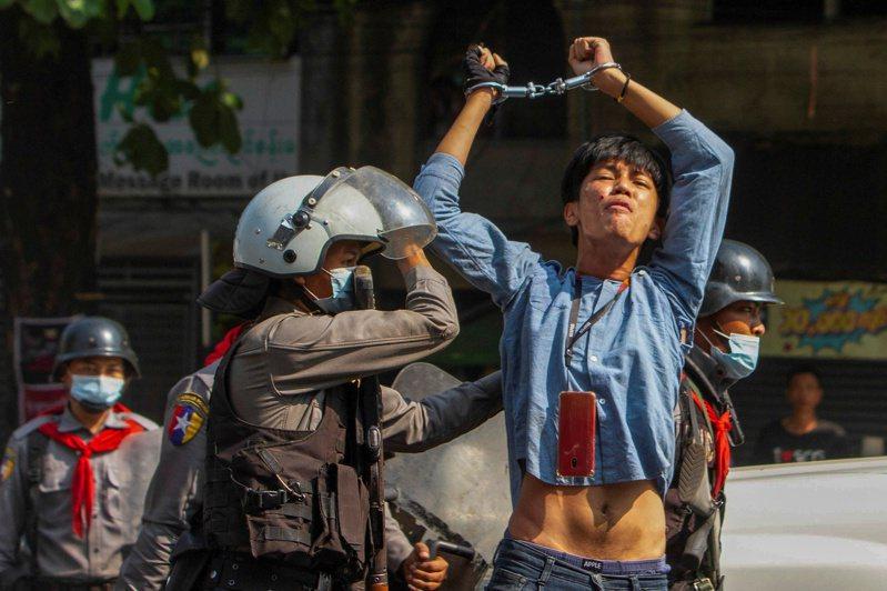 仰光市一名民主示威者27日遭鎮暴警察逮捕時,高舉戴上手銬的雙手。(路透)