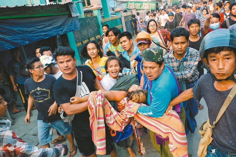 緬甸瓦城一名反政變示威者14日中彈,其他示威者將他抬離。(路透)