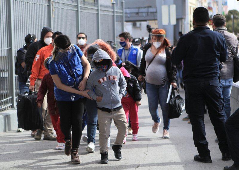 拜登政府為加快處理邊境無證移民問題的速度,已停止要求對提供照護的工作人員作背景調查。圖為工作人員安排無證移民兒童進入德州的收容中心。(歐新社)