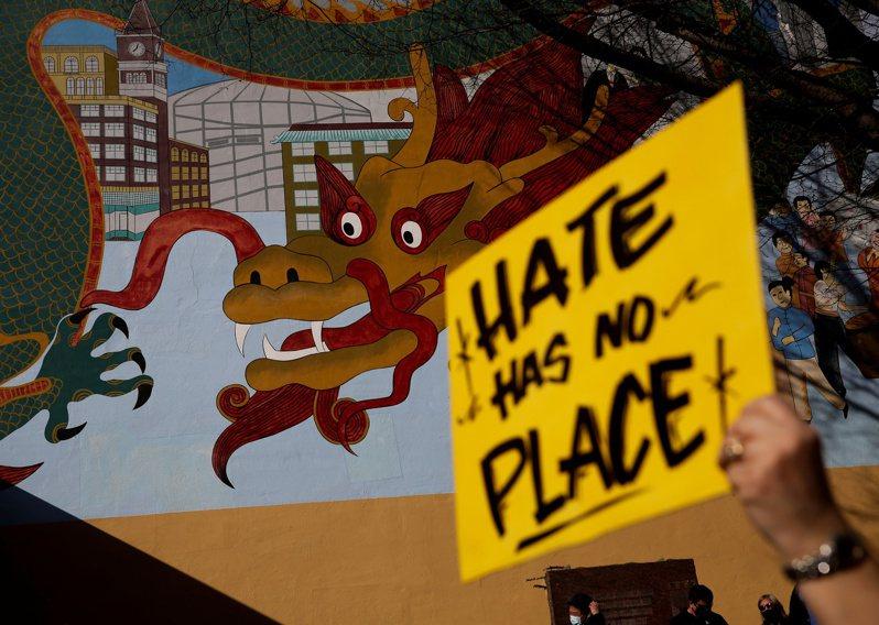 西雅圖的反仇恨犯罪活動,在龍壁畫前舉牌抗議。(路透)