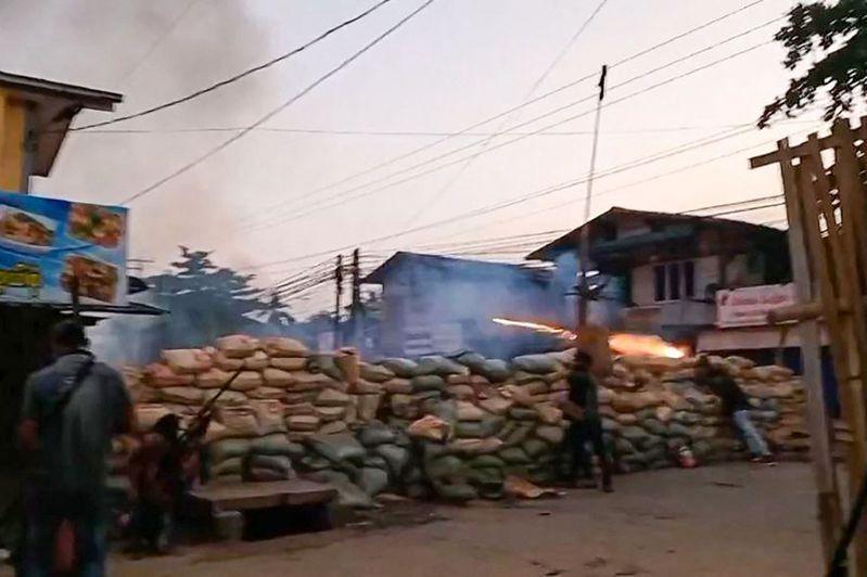 緬甸安全部隊9日在商業大城仰光附近城鎮勃固圍剿反政變群眾,示威者以沙袋為掩護躲避軍方槍彈。(Getty Images)