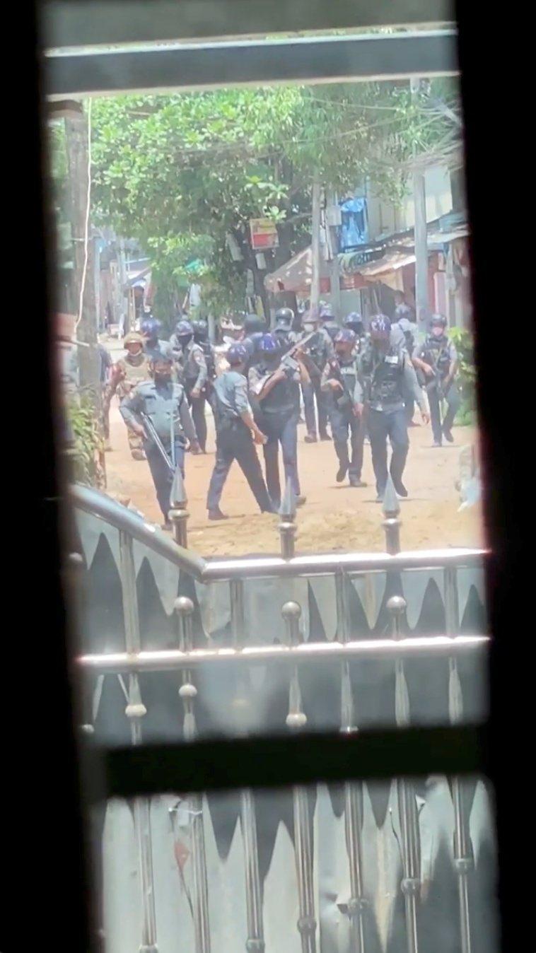 緬甸安全部隊在商業大城仰光附近城鎮勃固圍剿反政變群眾,民眾透過窗戶拍攝到安全部隊在街頭掃蕩的畫面。(路透)