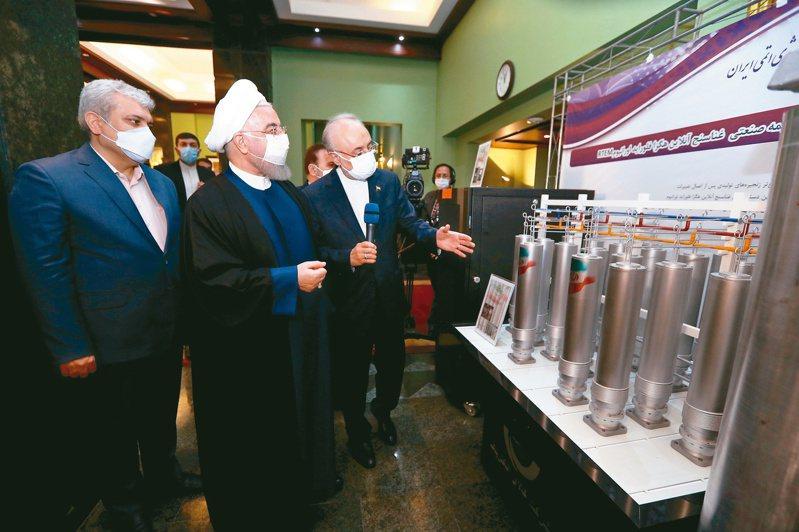 美國總統拜登有意撤銷對伊朗的部分制裁,換取伊朗重回核協議。圖為伊朗總統羅哈尼(中)10日參觀核研發成果展覽。(歐新社)