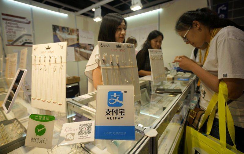 港府正與支付寶香港、八達通、Tap & Go(拍住賞)及WeChat Pay HK(微信港幣錢包)等4家支付工具營辦商商討發放5000港元電子消費券的細節安排。圖為香港商戶提供支付寶和微信支付等付款方式。(中新社)