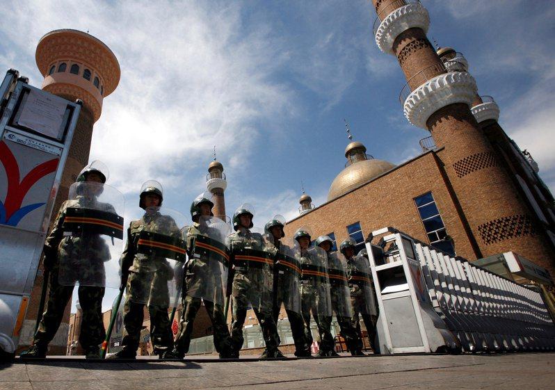 身穿防暴裝備的軍警在烏魯木齊市中心的一座大清真寺的入口處守衛。(路透資料照片)