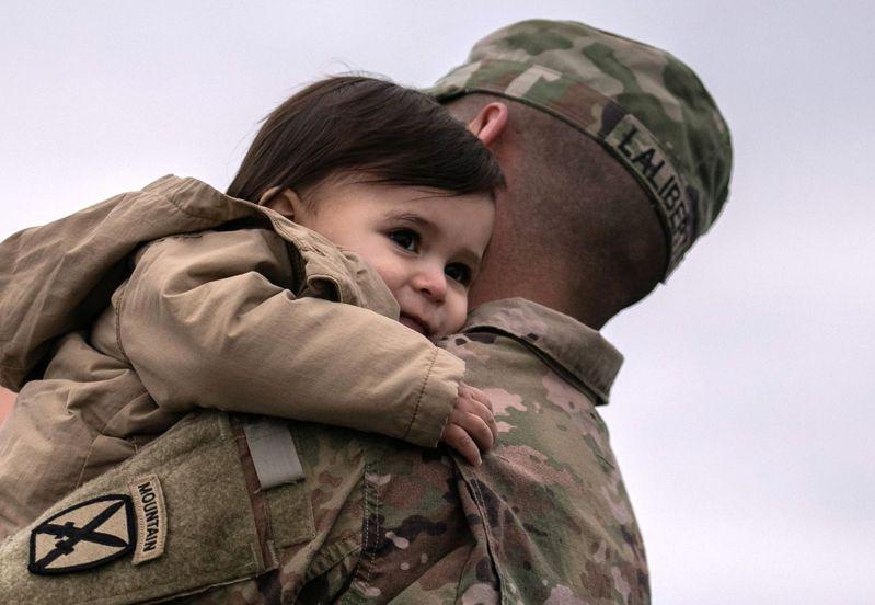 拜登政府13日宣布,9月11日前全部美軍自阿富汗撤軍;圖為自阿富汗返國的一名美軍在機場緊抱一歲的兒子。(Getty Images)