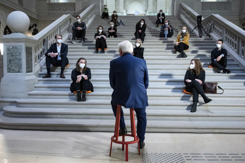 德國總統史坦麥爾(背對鏡頭者)12日在柏林國家圖書館階梯上對一群大學生發表演講完,接受提問。德國新冠確診病例當天突破300萬例。(美聯社)