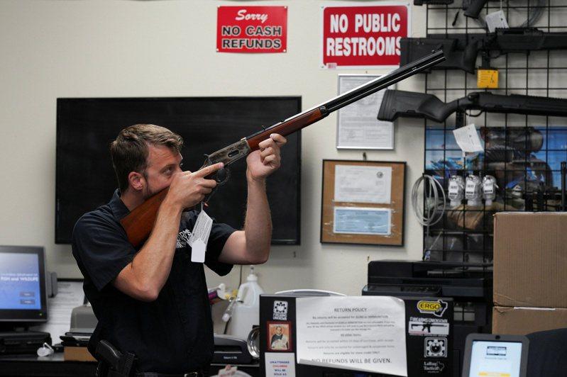 拜登總統呼籲國會盡快立法收緊槍支管制,但大規模基礎建設提案顯然要優先解決;圖為加州一間槍店的員工向顧客展示槍支。(路透)