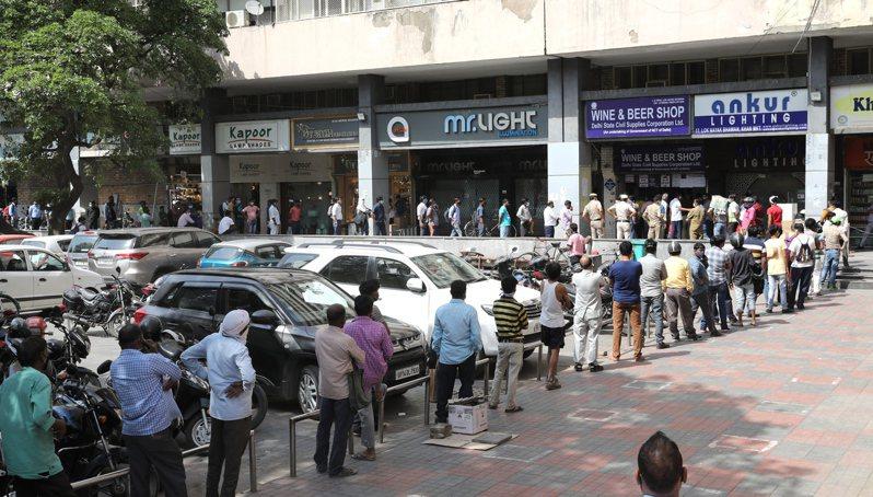 印度新德里19日晚間起將封城一周,大批民眾在一間酒鋪外大排長龍搶購。(歐新社)
