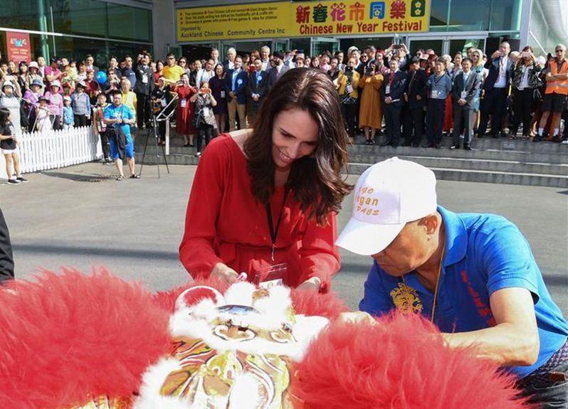圖為紐西蘭奧克蘭「新春花市同樂日」活動中,的舞獅表演。紐西蘭總理(前左)出席活動向華人拜年並為醒獅點睛。(取材自新華網)