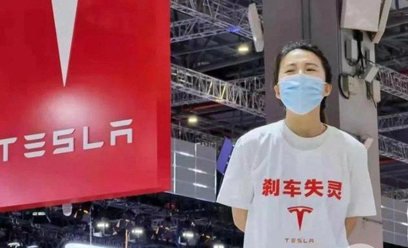 圖為19日上海車展開幕當天,穿著「剎車失靈」字樣T恤的女士,在特斯拉展區大聲呼喊「特斯拉刹車失靈」。(取材自上海證券報)