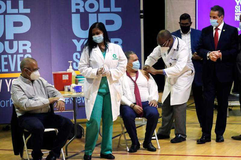紐約州府和市府24日宣布重新為民眾提供嬌生疫苗;圖為州長葛謨(右一)日前在曼哈頓哈林區參觀一間新開的免預約疫苗站。(Getty Images)