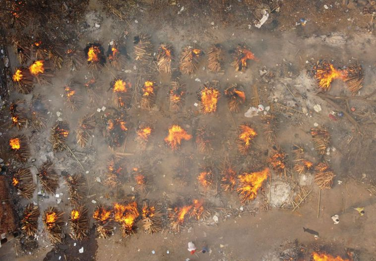 印度因新冠疫情死亡人數超過20萬,遺體在空地火化。從空中鳥瞰,一簇簇的火苗,令人...