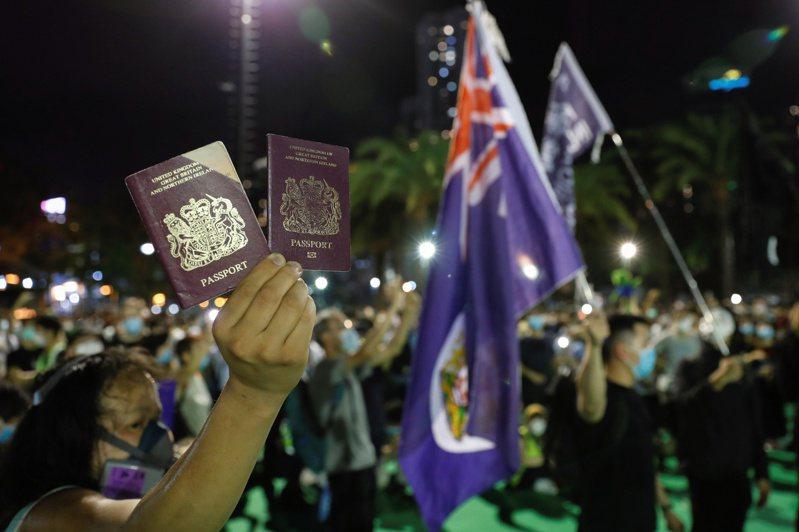 香港中文大學一項最新調查顯示,受訪的香港青年,半數決意移民。圖為港人在抗議活動時,高舉英國國民(海外)護照(BNO)。路透資料照片