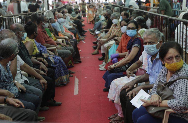 印度新冠疫情嚴重,日增40多萬例確診,創世界新高。圖為上周印度大城孟買市,居民排隊等候接種疫苗。(美聯社)