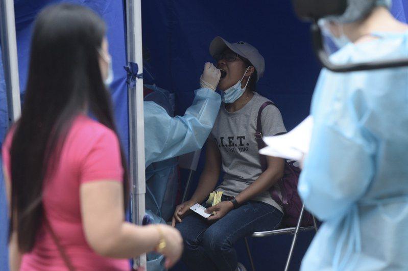 全港30多萬外傭將於5月9日前接受強制檢測。圖為外傭於香港中環一檢測採樣流動服務站排隊接受檢測。(中新社)