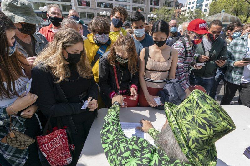 图为在纽约市,市民出示接种卡,就可获得免费大麻菸、啤酒等奖励。(美联社)(photo:UDN)