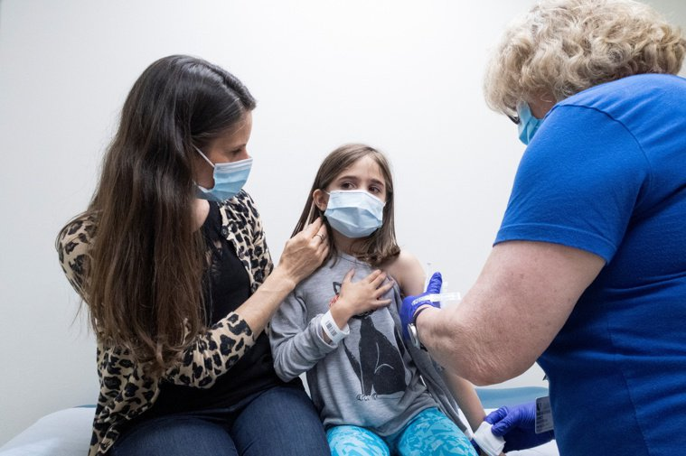 圖為北卡州一名女童在母親協助下,接種輝瑞疫苗。(路透)