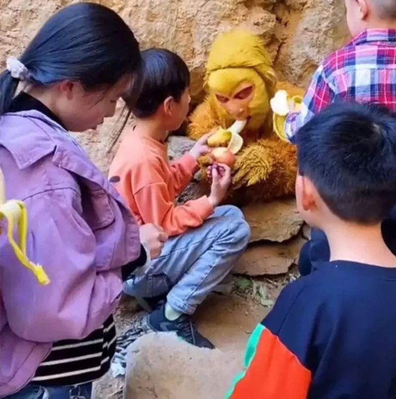 河北太行五指山景區內,一名工作人員扮成孫悟空,引起不少民眾圍觀餵食。(視頻截圖)