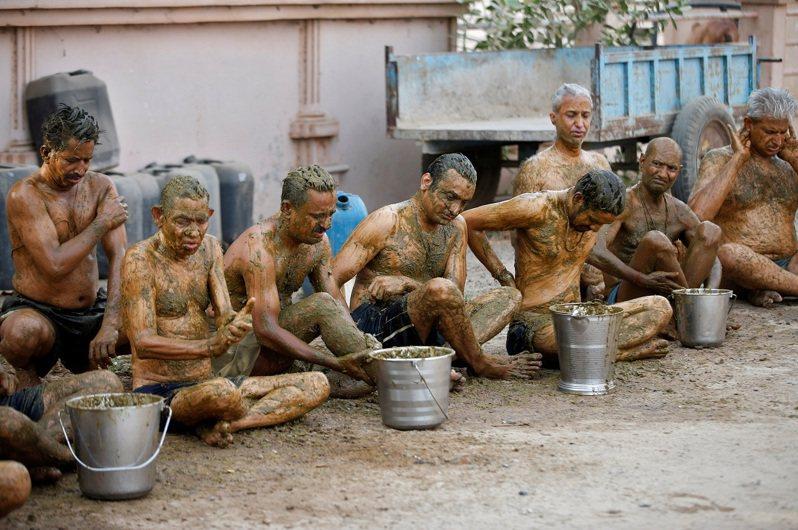 印度部分民眾相信牛糞療法,將牛糞塗在身上防疫。(路透)