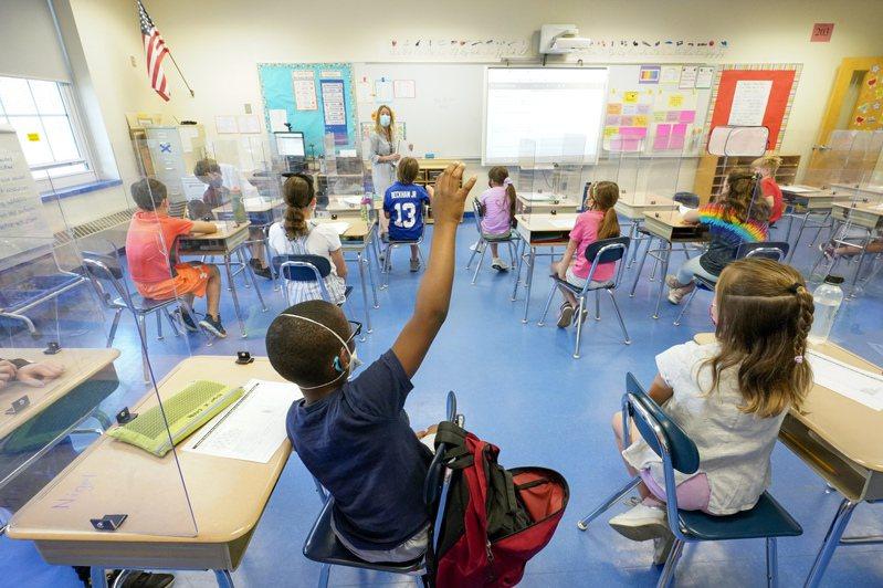 CDC指出,在學校要求師生戴口罩以及改善教室通風條件,可有效降低染疫風險;圖為紐約州一所公立學校的學生日前在教室內上課。(美聯社)
