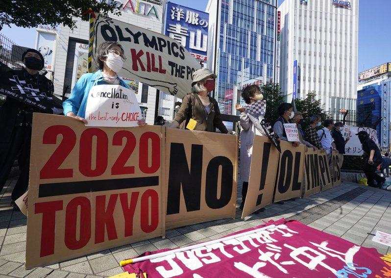 日本各界要求取消舉行奧運的呼聲越來越高。圖為東京市民23日在新宿舉牌要求取消東京奧運。 (歐新社)