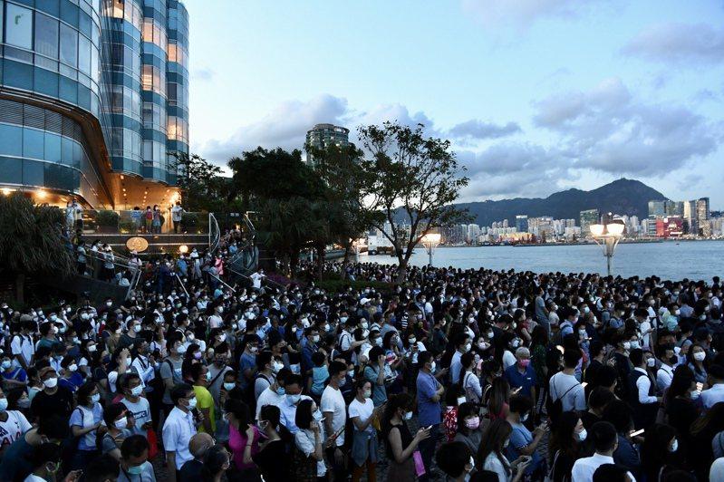 據香港中文大學醫學院學者經研究推斷,香港約有2萬名新冠病毒隱形患者。圖為大批市民戴著口罩,擠在黃埔海濱觀賞「超級月全食」。(中新社)