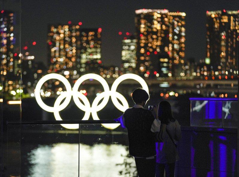 東京奧運官方合作夥伴的日本朝日新聞,發表社論呼籲首相菅義偉停辦東奧。圖為民眾站在位於東京台場奧運五環標誌前。 (歐新社)