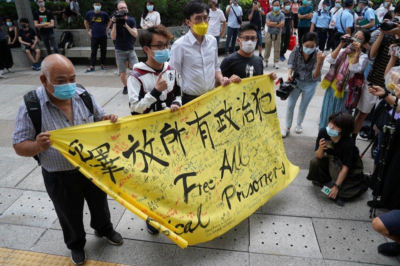 支持黎智英等十名泛民派人士的民眾,在香港法院前舉起布條要求釋放所有政治犯。(路透)