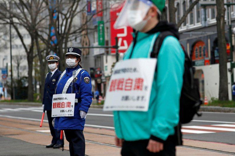 日本首相菅義偉在G7領袖峰會上,宣示日本將如期舉辦東京奧運及帕運的決心。圖為東京奧運會 5 日在札幌舉行男子和女子馬拉松測試賽,一名安保人員戴著寫著「為了防止感染,請不要觀看」標語。(路透)