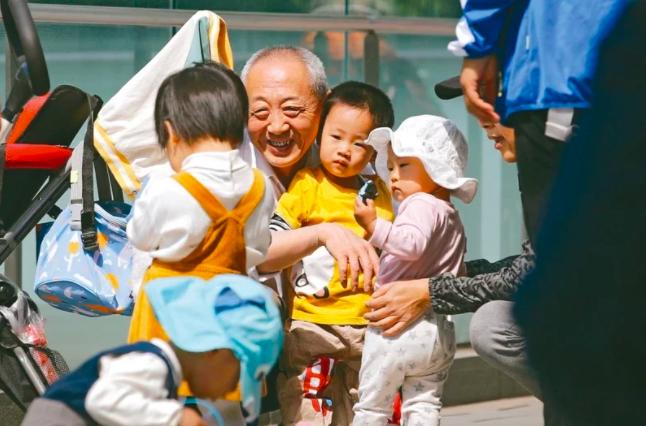 北京一名年長者與孩童在玩耍。 (美聯社)