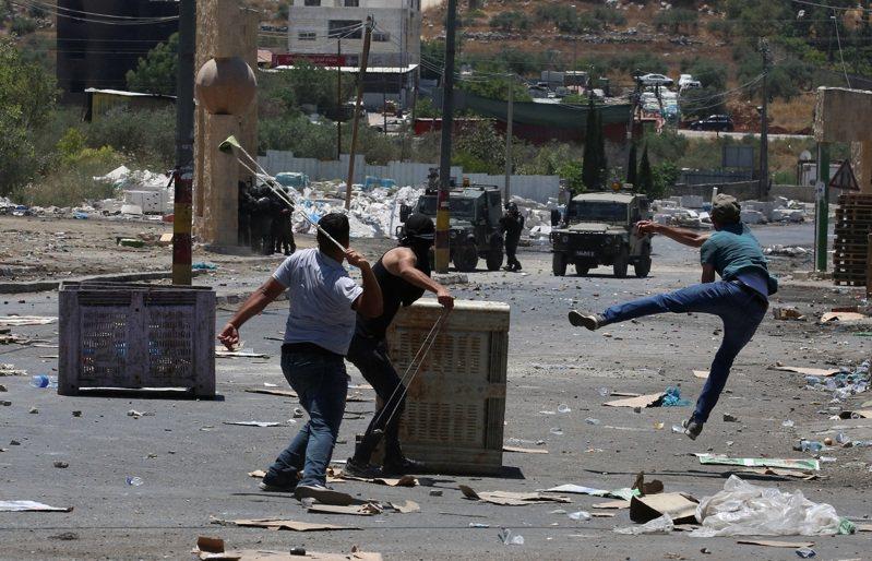 在約旦河西岸的納布盧斯,18日有巴勒斯坦人向以色列警察和軍人擲石頭,抗議以色列拓展猶太殖民區。(新華社)